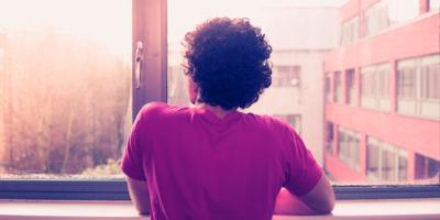 Junger Mann ist am Fensterbrett und schaut auf Sonnenuntergang hinaus