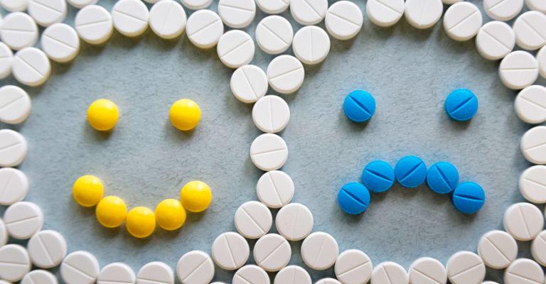 Tabletten zu einem Muster aus einem lachenden und einem traurigen Smilie gelegt