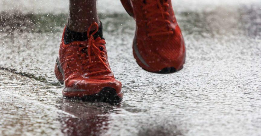 Nahaufnahme von Sportschuhen eines Athleten, der auf einem nassen Asphalt läuft. Spritzen Sie Wasser unter den Füßen hervor. Training im Regen.