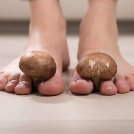 Nahaufnahme der Füße einer Frau mit essbaren Pilzen zwischen den Zehen