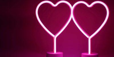 Zwei glühende rosa Neonherzen Valentinstag-Partykonzept