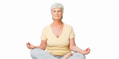 Ältere Frau sitzt in einer Lotussitzung und vermittelt auf dem Boden. Horizontale Aufnahme. Auf Weiß isoliert.