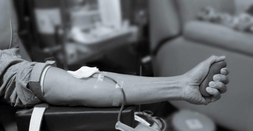 Arm des Blutspenders, der büscheligen Ball drückt. Blutspende.