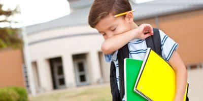 Junge in der Schule hustet in seinen Arm.