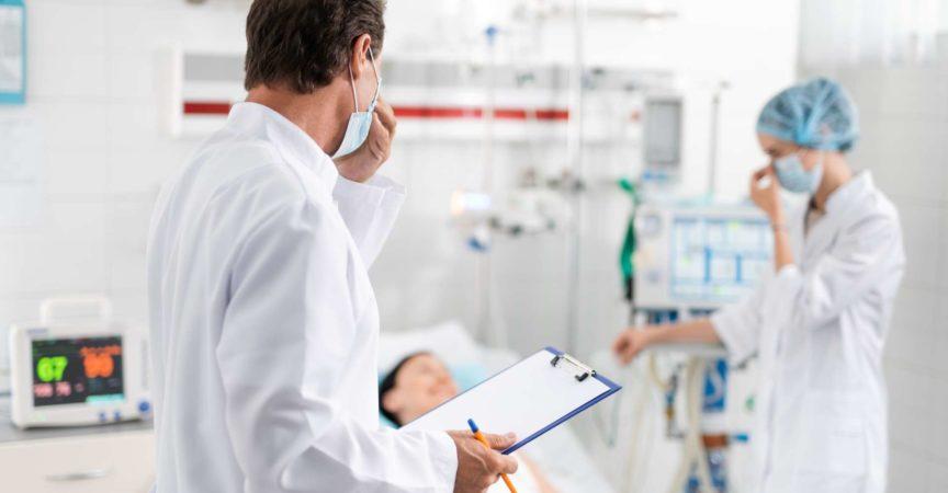 Doktor mit der medizinischen Form in der Hand, die Krankenschwester betrachtet, die nahe Patient steht