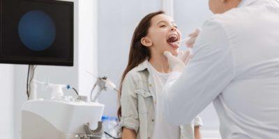 Kompetenter Arzt, der den Hals des kleinen Mädchens untersucht