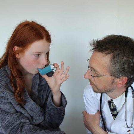 Krankenhausarzt zeigt junges Mädchen, wie man Salbutamol-Inhalator verwendet
