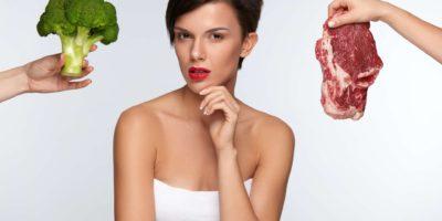 Gesunde schöne Frau, die zwischen Fleisch und Brokkoli wählt