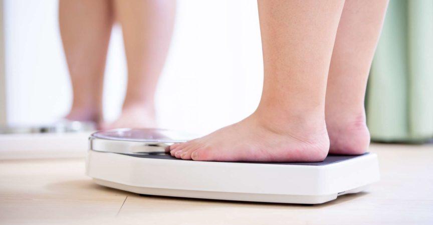 Plus Size Asian Girl Look Spiegel und messen Sie ihr Gewicht nach Waage