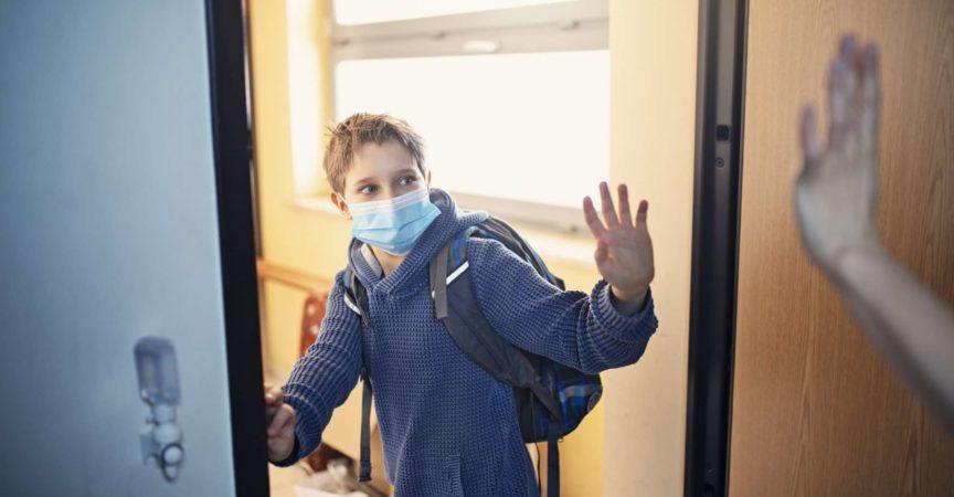 Kleiner Junge geht während der COVID-19-Pandemie zur Schule. Mutter winkt ihm zum Abschied und er winkt zurück. Nikon D850