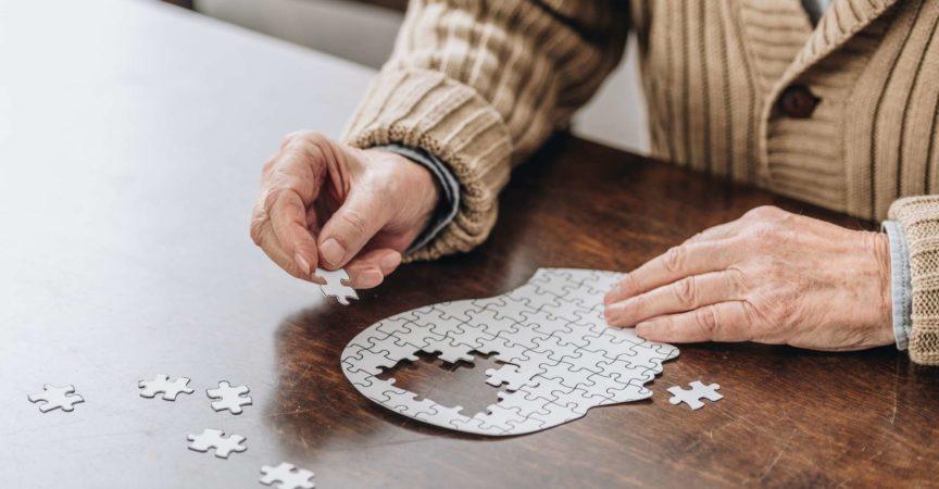 beschnittene Ansicht des älteren Mannes, der mit Rätseln spielt