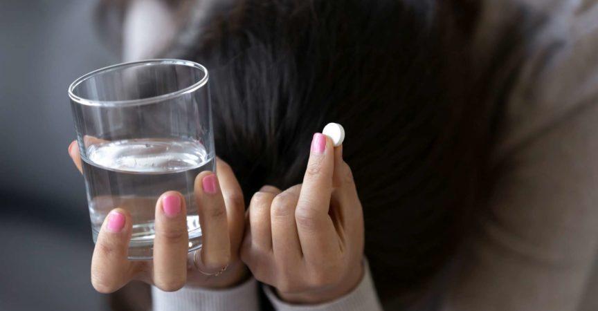 Traurige depressive Frau, die Pille und Glas Wasser hält