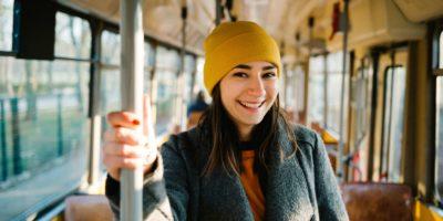 Junge Frau, die in einem Wagen einer fahrenden Straßenbahn steht. Transport-, Reise- und Lifestyle-Konzept.
