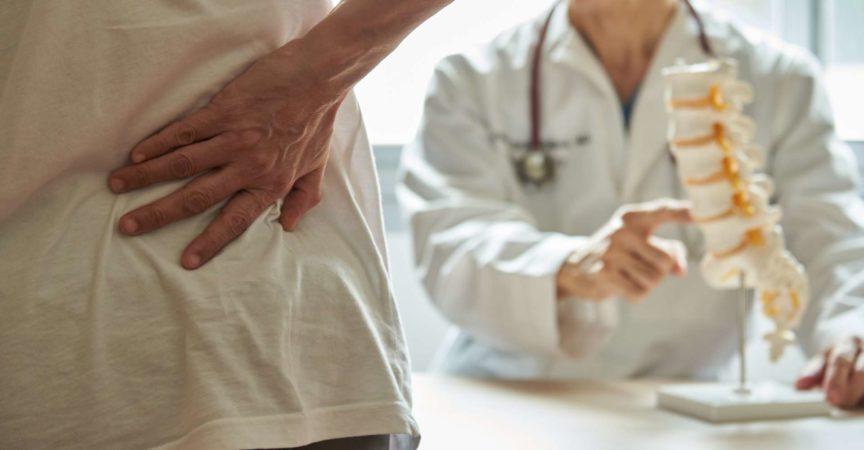 Ein männlicher Arzt erklärt der Patientin die Anatomie der Lendenwirbelsäule und klagt in der medizinischen Klinik über Rückenschmerzen