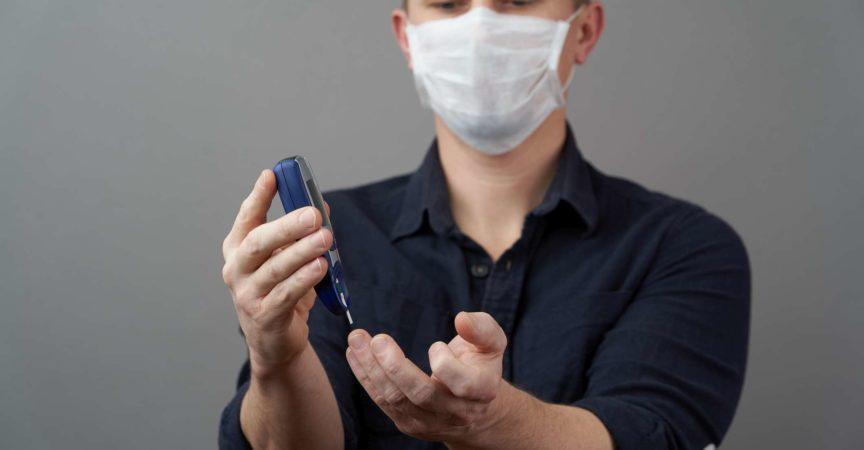 Mann, der Blutzuckerspiegel mit Glukometer auf grauem Hintergrund prüft