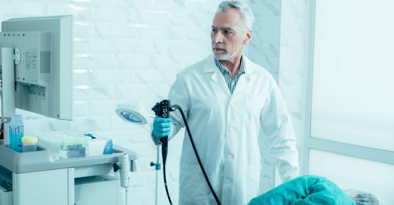 Ernsthafter reifer Arzt, der ein modernes Endoskop hält und sich auf das Verfahren vorbereitet