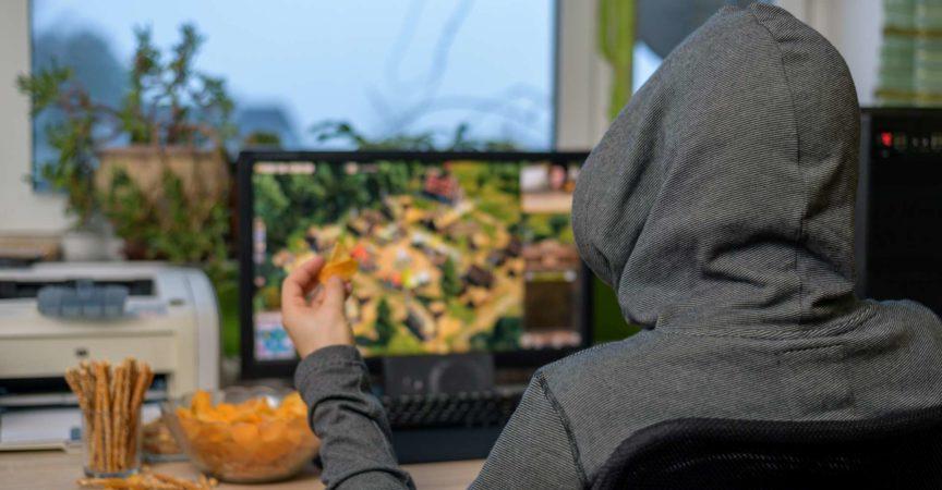 männlicher Spieler, der Strategiespiel auf Computer spielt, der Snacks isst