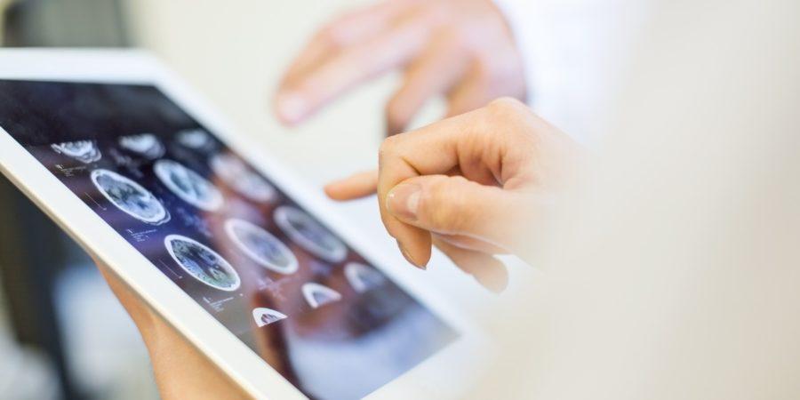 Medizinisches Team analysiert MRT-Scans auf einem digitalen Tablet