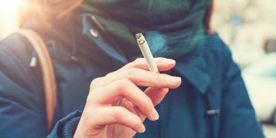 Junge Frau, die eine Zigarette genießt