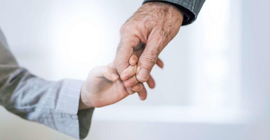 Hand Nahaufnahme von Großvater und Enkelin Händchen haltend.