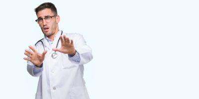Doktor Mann Angst und Angst vor Angst Ausdruck Stop Geste mit den Händen, vor Schock schreien. Panikkonzept.