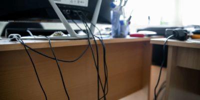 Konzept der Unordnung im Büro. Abgewickelte und verwickelte elektrische Drähte unter dem Tisch. 5S-System der schlanken Fertigung