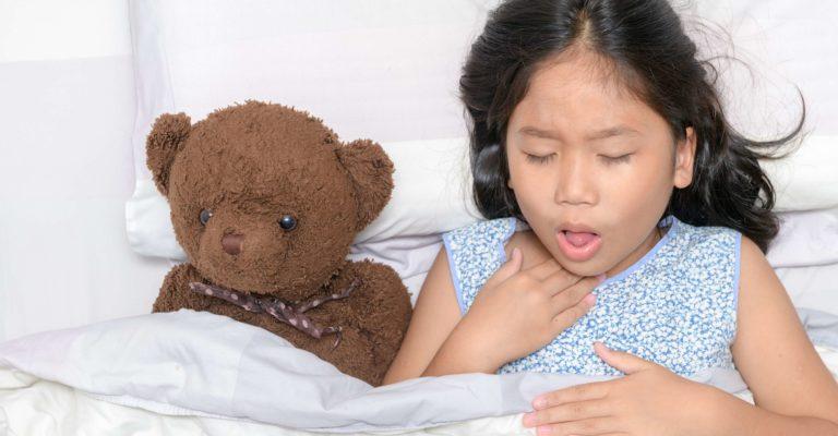 Kleines Mädchen hustet und Halsschmerzen, die auf Bett mit Spielzeugbär liegen, Gesundheitskonzept