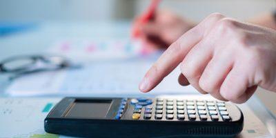 Nahaufnahme des Unternehmers, der Buchhaltungsdokument am Schreibtisch im Büro analysiert