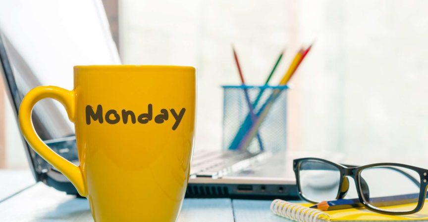 Montag geschrieben auf gelbe Kaffee- oder Teetasse am hölzernen Brettertisch, am Arbeitsplatz, im Bürosonnenlichtmorgenhintergrund.