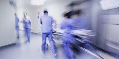 Ärzte und Krankenschwestern ziehen Krankenhauswagen,
