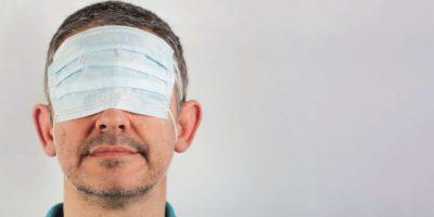 isolierter Mann mit verbundenen Augen mit chirurgischer Maske über den Augen und nacktem Mund und Nase