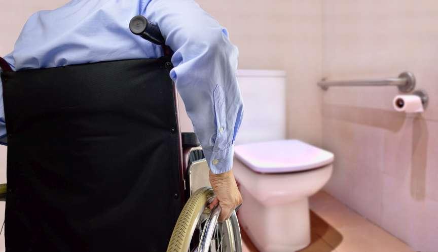 Rückansicht des Mannes im Rollstuhl, der zur Toilette geht, angepasst für behinderte Person