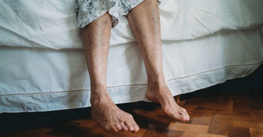 Vorderansicht der Füße einer älteren Dame auf der Seite des Bettes. Parkettboden. Konzentriere dich auf die Füße.