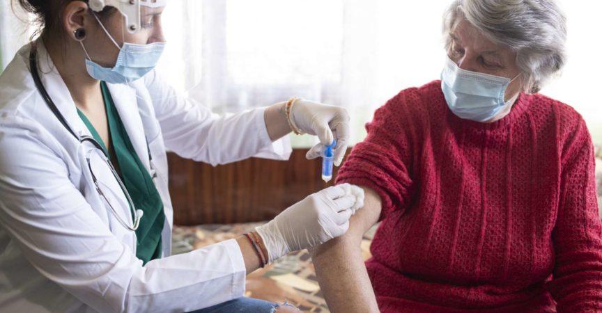 Weibliche Gesundheitsperson, die der älteren Frau in ihrem Haus Impfstoff injiziert.