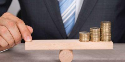 Mittelteil des Geschäftsmannes, der Münzen auf hölzerner Wippe am Tisch balanciert