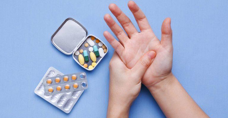 Frauenhand mit Gelenkschmerzen und Pillen auf Tisch