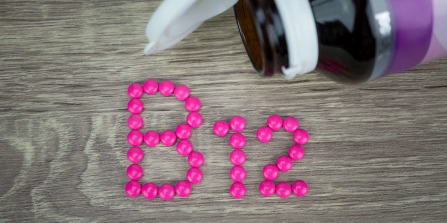 Rosa Pillen, die Form zu B12-Alphabet auf Holzhintergrund bilden