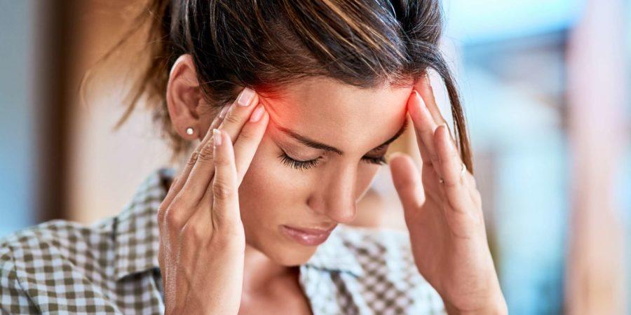Aufnahme einer unbequem aussehenden Frau, die ihren Kopf aufgrund von Schmerzen zu Hause während des Tages unbehaglich hält