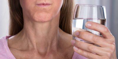 Nahaufnahme der Frau, die mit Wasser im Glas spült und gurgelt