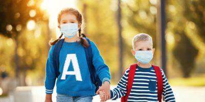 Fröhliche Geschwister in Schutzmasken mit Schulrucksäcken