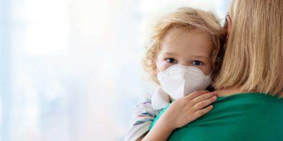 Mutter und Kind mit Gesichtsmaske und Händedesinfektionsmittel