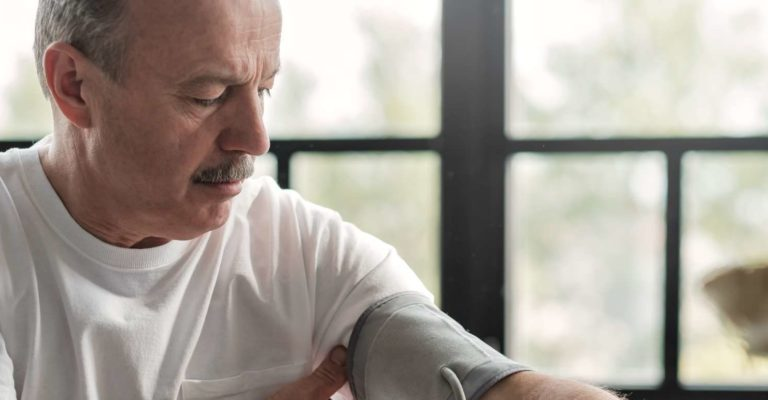 Alter hispanischer Mann, der sich schlecht fühlt, wenn er morgens mit einem Blutdruckmessgerät zu Hause seine Gesundheit überprüft