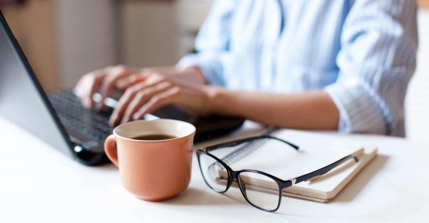 Fernarbeit von zu Hause aus. Freiberuflicher Arbeitsplatz in der Küche mit Laptop, Tasse Kaffee