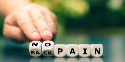 """Die Hand dreht die Würfel und ändert den Ausdruck """"Rückenschmerzen"""" in """"keine Schmerzen""""."""