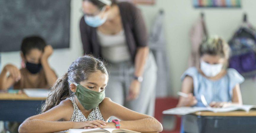 12 Jahre altes Mädchen, das eine wiederverwendbare, schützende Gesichtsmaske im Klassenzimmer trägt, während an der Schularbeit an ihrem Schreibtisch gearbeitet wird.