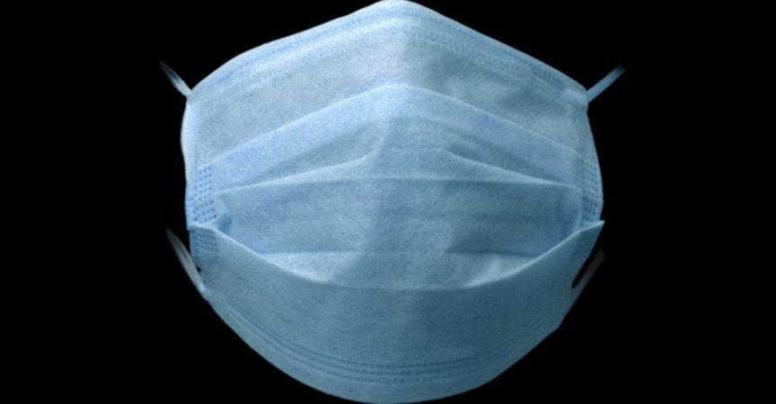 Schützende Gesichtsmaske auf farbigem Hintergrund. Farbe Hartfaserplatte