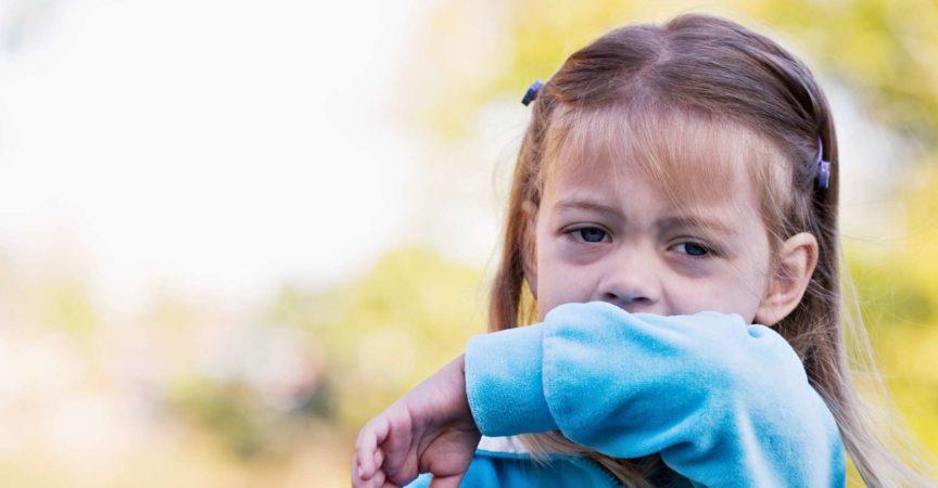 Ein kleines Mädchen, das niest, um den Ellbogen zu bekommen