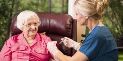 Krankenschwester im häuslichen Gesundheitswesen, die einer älteren Frau eine Injektion gibt.