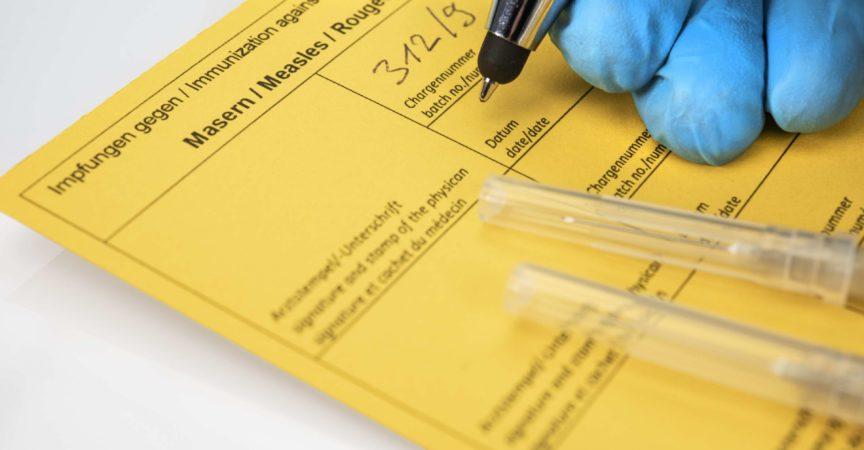 Gesundheitskonzept: Hände eines Arztes mit Nitrilhandschuhen neben Spritzen und einem Impfpass. Konzept für die Diskussion um die Impfpflicht.