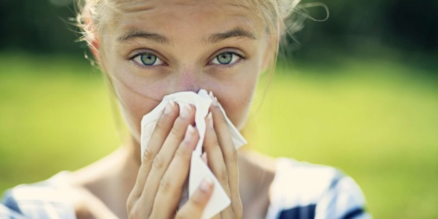Porträt eines jugendlichen Mädchens, das sich an einem Sommertag die Nase putzt. Das Mädchen ist allergisch gegen die Pollen.